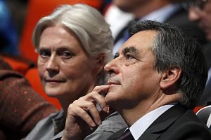 Mr Fillon and his wife Penelope at a rally in Paris. The conservative former prime minister had seemed likely to win the presidency until a media report last week accused his wife of receiving a salary from fake jobs.