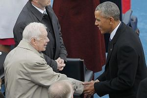 Former US president Jimmy Carter and Mr Obama greeting each other at Mr Trump's inauguration earlier this month.