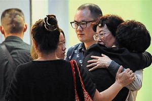 Family members of victims of the catamaran that sank on its way to Pulau Mengalum consoling each other.