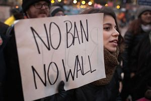 Demonstrators at O'Hare Airport in Chicago protesting US President Donald Trump's executive order, which imposes a freeze on admitting refugees into the country and a ban on travel from seven Muslim-majority countries.