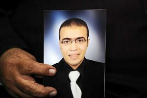 Abdullah Reda al-Hamamy in a photo held by his father during an interview with Reuters.
