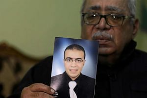 Reda Abdullah al-Hamamy holds a picture of his son during an interview with Reuters in Daqahliya, Egypt, Feb 4, 2017.