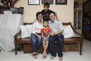 Ms Low and her husband, financial controller Christopher Lim, 45, play Monopoly with their sons Cedric (standing), nine, and Clement, seven, to teach them skills, such as how to calculate if they can afford something.
