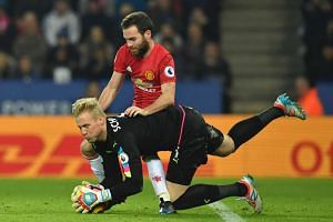 Leicester City's Danish goalkeeper Kasper Schmeichel makes a save to prevent Manchester United's Spanish midfielder Juan Mata having a shot on goal during the English Premier League football match on Feb 5, 2017.