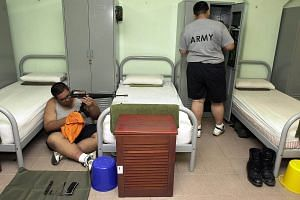 Recruits at the Basic Military Training Centre (BMTC) at Pulau Tekong cleaning their weapons in their barracks at night.