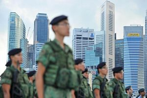 Singapore Armed Forces servicemen standing at attention against the backdrop of Central Business District during the Second National Education show for National Day Parade 2014 held at The Float@Marina Bay on July 19, 2014.