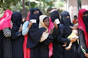 Rohingya women wait in a queue with vouchers to collect relief distributed by the Bangladesh Red Crescent Society on Feb 6, 2017.