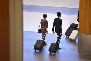 A Singapore Airlines air stewardess and an air steward returning from a flight at Changi Airport Terminal 2.