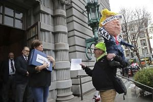 A woman handing out the 9th Circuit Court of Appeals' ruling against President Trump's travel ban and a demonstrator with a President Trump pinata outside the courthouse in San Francisco, on Feb 9, 2017.