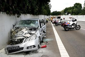 Lim (above) being led away after the AYE crash last year. He allegedly drove his Mercedes-Benz (left) into oncoming traffic.