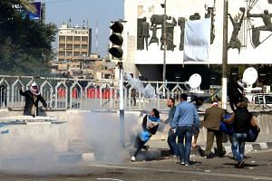 Protesters run from tear gas fired by security forces after supporters of Iraqi Shi'ite cleric Moqtada al-Sadr tried to approach the heavily fortified Green Zone.