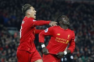 Liverpool's Sadio Mane celebrates scoring their first goal with Roberto Firmino.