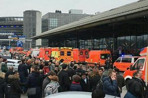 People wait outside the Hamburg Airport after an unknown substance that caused eye irritation among staff was found in the security check area.
