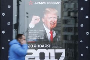 A pedestrian walks past a Russian store with a poster of President Donald Trump on it. Phone records and intercepted calls have revealed that Trump's campaign aides had repeated contacts with Russian intelligence.