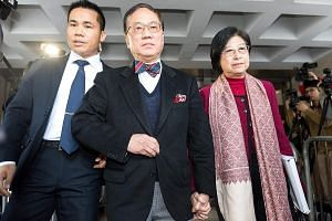 Donald Tsang (centre) leaving the High Court yesterday with his wife Selina, accompanied by a security officer. He has pleaded not guilty to three charges of misconduct and bribery.