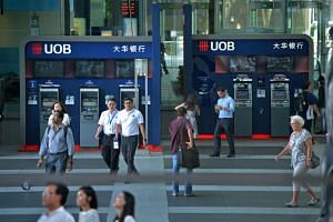 Office workers walking past the UOB ATMs at Raffles Place.