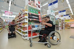 Wheelchair users shop in a supermarket with lower shelves at Enabling Village.