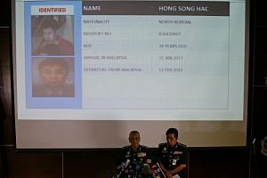Malaysia's National Police Deputy Inspector-General Noor Rashid Ibrahim (front, left) speaking in front of a screen showing North Korean suspect Hong Song Hac during a news conference regarding the apparent assassination of Kim Jong Nam, in Kuala Lum