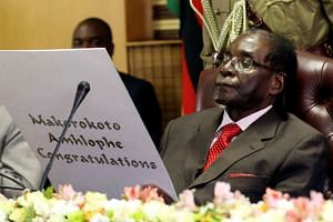 Zimbabwe's President Robert Mugabe reads a card during his 93rd birthday celebrations in Harare, Feb 21, 2017.