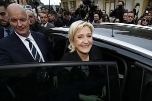 Marine Le Pen (centre), flanked by her bodyguard Thierry Legier (left), entering a car after visiting the French-Italian border during an election campaign visit in Menton, France on Feb 13, 2017.