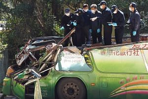 Investigators examining the wreckage of a tourist bus to try to find out the cause of the crash that killed 33 people and injured 11 in Taipei last week.