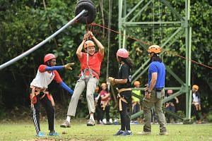 Education Minister (Schools) Ng Chee Meng trying out flying fox at the Outward Bound Singapore (OBS) facility on Pulau Ubin on Thursday (Feb 23)