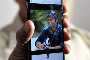 Jagan Mohan Reddy holds a smartphone with an image of his son Alok Madasani at his residence in Hyderabad, India.