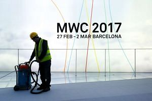 A laborer vacuums at the conference center ahead of the Mobile World Congress (MWC) in Barcelona, Spain, on Saturday, Feb. 25, 2017.