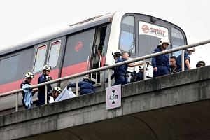 SCDF personnel working at the site of an accident which left two SMRT trainees dead after a train ran into them, on March 22, 2016.