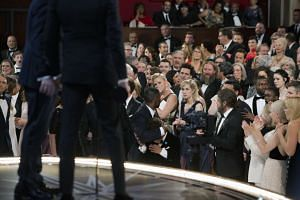 Members of the audience reacting as Moonlight was named best picture, moments after La La Land was mistakenly announced as the winner first.