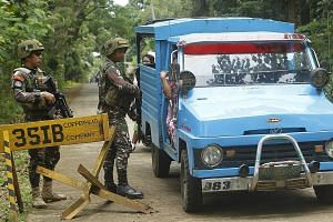 Philippine soldiers manning a checkpoint in Sulu yesterday. The province is home to the Abu Sayyaf, a group notorious for holding Filipinos and foreigners alike for ransom. Still, the Philippine Foreign Secretary says the country will stick to its to