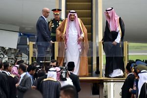 Saudi Arabia's King Salman bin Abdul Aziz (centre) smiles as he arrives at Halim airport in Jakarta on March 1, 2017.