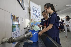 Secondary 2 students Chia Jia En (left) and Koh Wei Shan relying on water in a pail to wash their hands during the water rationing exercise at Woodgrove Secondary School yesterday. Woodgrove is the first of 45 schools, including pre-schools, to condu