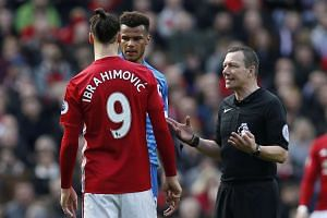 Ibrahimovic and Mings are spoken to by referee Kevin Friend.