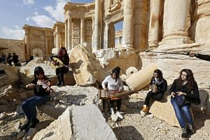 Syrian women playing musical instruments amid the ruins of Palmyra on March 4, 2017.