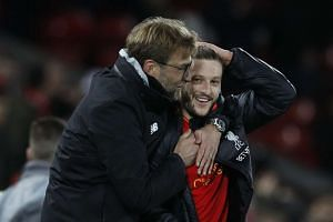 Klopp celebrates after the game with Liverpool's Adam Lallana.
