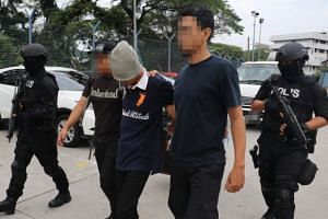 Malaysian police escorting one of the seven men who were arrested for suspected links to terror organisations.
