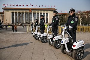 Police officers patrol Tiananmen Square in front of the Great Hall of the People yesterday. NPC spokesman Fu Ying (above) spoke to local and foreign media ahead of the opening of the NPC's annual session today.