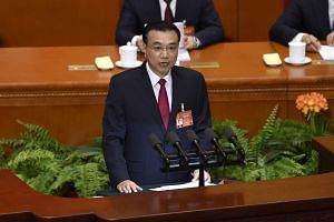 Chinese Premier Li Keqiang delivering his report during the opening session of the National People's Congress in the Great Hall of the People in Beijing on March 5, 2017.
