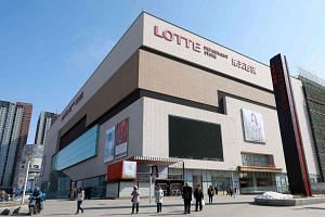 People walking past a Lotte Department Store in Shenyang, north-east China's Liaoning province.