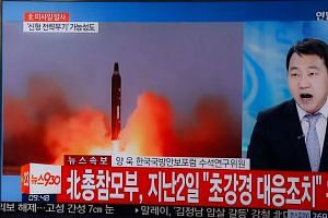 A TV screen displays a news broadcast on North Korea's missile launch at a Seoul station on March 6, 2017.