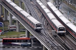 A SBS bus passes under moving SMRT trains along Ang Mo Kio Ave 1. The Ministry of Transport announced new initiatives during the Budget debate in 2017.