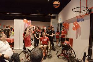 Minister for Culture, Community and Youth Grace Fu tries shooting hoops in a wheelchair, under the guidance of the Wheelchair Basketball association members at a para sports day event.