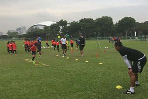 ActiveSG Football Academy participants training at the Kallang Cricket Field.