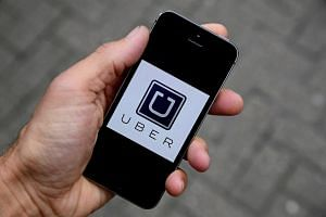 The Uber app logo is seen on a mobile telephone.