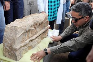 Antiquities Minister Khaled al-Anani inspects an unearthed statue that workers say depicts revered Pharaoh Ramses II in Cairo, Egypt, on March 9, 2017.