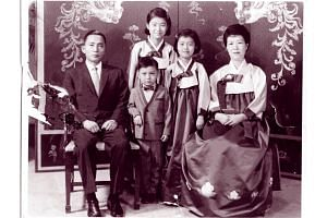 Handout photo of Park Geun Hye posing with her father and then-President Park Chung Hee and her mother Yuk Young Soo along with her younger brother and sister in Seoul.