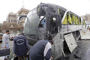 Syrian forensics experts examining a damaged bus at the scene of a suicide bombing in Damascus' Old City on March 11, 2017.