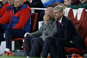 Arsenal's French manager Arsene Wenger (R) looks on from the dugout in the match against Lincoln.