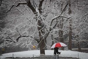 A man holds an umbrella as he walks through the snow in Central Park, New York, on March 10, 2017.